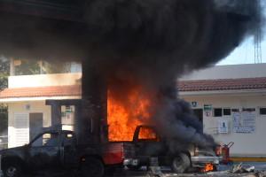 """MEX01. PUERTO VALLARTA (MÉXICO), 01/05/2015.- Vista de dos vehículos quemados al interior de una estación de gasolina hoy, viernes 1 de mayo de 2015, en la ciudad de Puerto Vallarta, estado de Jalisco (México). Al menos un policía y varios delincuentes murieron por los narcobloqueos que se están produciendo en al menos una veintena de puntos en el occidental estado mexicano de Jalisco, informaron fuentes oficiales. Desde primeras horas de la mañana se están produciendo bloqueos de calles e incendios de vehículos y comercios en al menos 20 lugares que dejan hasta el momento un policía muerto y un número """"no determinado de delincuentes"""" muertos y heridos, confirmó hoy el gobierno de esa entidad. EFE/Francisco Pérez"""