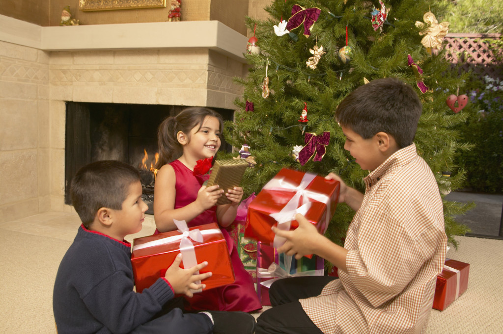 Three children with gifts on Christmas eve