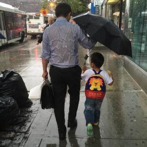 Papá se empapa al evitar que se moje su hijo